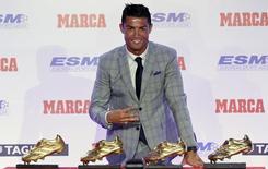 Atacante Cristiano Ronaldo, do Real Madrid, posa em frente dos quatro prêmios Chuteira de Ouro que conquistou durante cerimônia em Madri. 13/10/2015 REUTERS/Andrea Comas