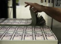 Plantillas con billetes de cinco dólares en la Casa de la Moneda de Estados Unidos en Washington, mar 26, 2015. El dólar subía el jueves contra una canasta de monedas, después de que la inflación subyacente en Estados Unidos se fortaleció más de lo esperado en septiembre, lo que revivió algunas expectativas de que la Reserva Federal subiría las tasas de interés este año. REUTERS/Gary Cameron