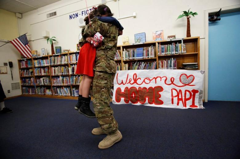 California Army National Guard helicopter pilot David Duran hugs his daughter Luz after surprising her on Valentine's Day at Gates Elementary School in Los Angeles, California February 14, 2014. Duran had just returned from a year's deployment in Afghanistan.  REUTERS/Mario Anzuoni