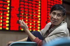 Un inversor frente a un tablero electrónico que muestra la información de las acciones, en una correduría en Nanjing, China, 16 de octubre de 2015. Las acciones chinas subieron el viernes a máximos en siete semanas, y los principales índices bursátiles del país registraron su mejor desempeño semanal en cuatro meses y medio después de que datos mostraron que los préstamos chinos aumentaron en septiembre. REUTERS/China Daily