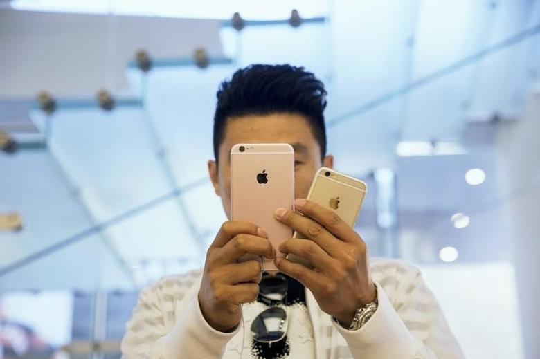 A man takes pictures as Apple iPhone 6s and 6s Plus go on sale at an Apple Store in Beijing, China September 25, 2015. REUTERS/Damir Sagolj