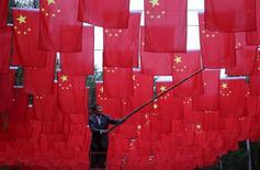 Homem colocando bandeiras chinesas em parque em Pequim.  29/09/2015   REUTERS/China Daily