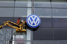 Workers clean the facade of a Volkswagen dealership near the Andalusian capital of Seville, southern Spain, October 16, 2015. REUTERS/Marcelo del Pozo