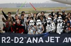 "Cosplayers, dressed up as characters from ""Star Wars"", wave in front of an All Nippon Airways (ANA) Boeing 787-9 Dreamliner JA873A named the ""R2-D2 ANA JET"" during a fan flight event at Haneda airport October 17, 2015. REUTERS/Yuya Shino"
