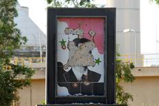 Поврежденный портрет президента Сирии Башара Асада в провинции Хама 29 июля 2015 года. Турция допустила компромиссное временное сохранение у власти опирающегося на поддержку Москвы сирийского президента Башара Асада, ухода которого добивается Запад. REUTERS/Ammar Abdullah