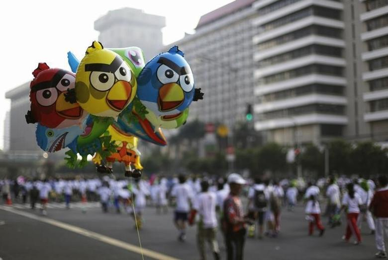 Angry Birds balloons are seen as people run during Car Free Day at the main street in Jakarta July 8, 2012.  REUTERS/Beawiharta