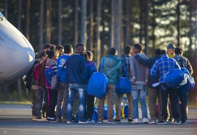 Eritrean migrants arrive at Lulea airport, Kallax in northern Sweden, with an Italian police aircraft that took off from Rome's Ciampino airport earlier on Friday, October 9, 2015. REUTERS/Robert Nyholm/TT News Agency