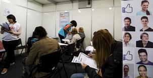 Pessoas preenchendo fichas de emprego em São Paulo.  11/05/2015    REUTERS/Paulo Whitaker