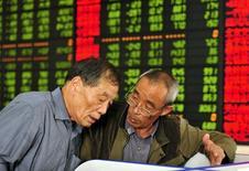 Inversores hablan mientras miran la pantalla de un computador que muestra la información de las acciones en una correduría en Fuyang, China, 21 de octubre de 2015. Las acciones chinas rebotaron más de un 1 por ciento el jueves, luego de que el declive de un 3 por ciento de la sesión anterior creara una oportunidad de compra para algunos inversores que se perdieron un repunte reciente. REUTERS/Stringer