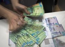 Работник отделения Евразийского банка считает деньги. 15 января 2015 года. Нацбанк Казахстана потратит 1 триллион тенге ($3,6 миллиарда) из государственного пенсионного фонда в следующем году с целью поддержать замедляющийся экономический рост, сказал председатель ЦБ Кайрат Келимбетов. REUTERS/Shamil Zhumatov