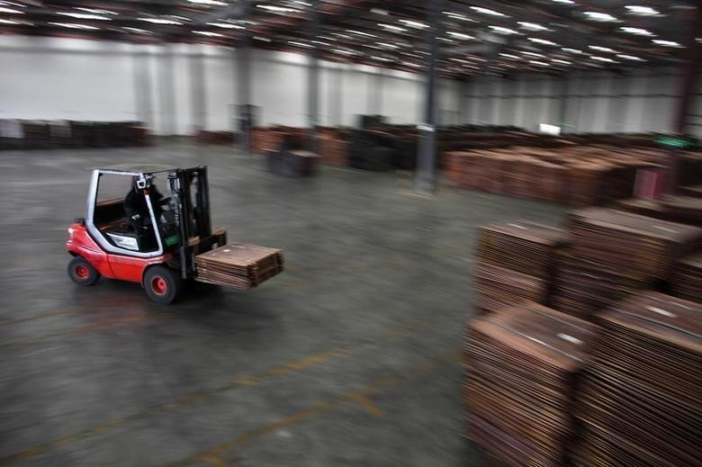 图为上海洋山港附近一家仓库,一名工人在搬运铜。REUTERS/Carlos Barria