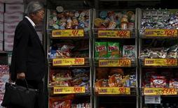 Мужчина проходит мимо магазина в Токио. 25 мая 2015 года. Японии нужно осуществить запланированное повышение налога с продаж, чтобы увеличить доходы бюджета и снизить внушительный государственный долг, считает международное рейтинговое агентство Standard & Poor's. REUTERS/Yuya Shino