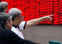 Un inversor apunta a un tablero electrónico que muestra la información de las acciones, en una correduría en Nanjing, 23 de  octubre de 2015. Las acciones chinas cerraron con un leve avance el lunes después de que el banco central de China recortó las tasas de interés por sexta ocasión desde noviembre para apoya a la economía, pero los avances fueron limitados por una toma de ganancias. REUTERS/China Daily
