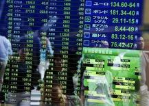 Peatones se reflejan en una pantalla que muestra la información de las acciones de varios países, en una correduría en Tokio, Japón, 29 de septiembrede de 2015. Las bolsas de Asia se acercaban el lunes a borrar todas sus pérdidas desde la sorpresiva devaluación de la moneda china en agosto, gracias a un repunte de las acciones globales luego de que el banco central de China recortó las tasas de interés. REUTERS/Issei Kato