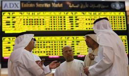 Инвесторы на фондовой бирже в Абу-Даби. 25 июня 2014 года. Новым размещениям на фондовой бирже Абу-Даби придется подождать, пока ситуация на рынке не улучшится, сказал исполнительный директор биржи. REUTERS/Stringer