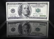 Ilustración fotográfica de un billete de 100 dólares, tomada en Tokio, 2 de agosto de 2011. Una subida del dólar desde el verano boreal del año pasado, de casi 20 por ciento está afectando a las exportaciones de Estados Unidos y reduciendo las ganancias corporativas allí, socavando a la mayor economía mundial y a uno de sus dos motores de crecimiento. REUTERS/Yuriko Nakao