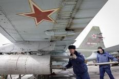 Инженеры загружают ракеты в истребитель Су-25 во время учений в Ставропольском крае. 12 марта 2015 года. Родители 19-летнего солдата, чей уход из жизни стал первой подтвержденной смертью российского военного в Сирии после четырех недель авиаударов, заявили во вторник, что не верят версии о суициде, которой придерживается командование. REUTERS/Eduard Korniyenko