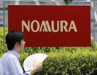 Мужчина проходит мимо логотипа Nomura Holdings в Токио. 29 июля 2015 года. Nomura Holdings Inc снизила чистую прибыль в третьем квартале на 12 процентов в годовом исчислении на фоне сохраняющейся волатильности мировых рынков, связанной с  замедлением экономического роста Китая и неопределенностью сроков повышения ставки ФРС США. REUTERS/Toru Hanai