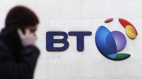 Un hombre habla por celular mientras camina delante del logo de BT, en Londres, 5 de febrero de 2015.  Gran Bretaña autorizó provisionalmente el miércoles el acuerdo de BT para comprar al operador móvil EE en una operación valorada en 12.500 millones de libras (19.000 millones de dólares) que formará el principal operador de banda ancha, líneas fijas y móviles del país. REUTERS/Suzanne Plunkett