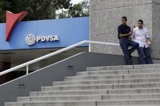 Unas personas en un edificio junto a una gasolinera de PDVSA en Caracas, oct 28, 2015. La estatal venezolana PDVSA reportó ingresos generales por 59.180 millones de dólares en el primer semestre de 2015, cifra que es casi la mitad de todo el año pasado pese al desplome del precio del petróleo, dijo el miércoles su presidente, Eulogio Del Pino.  REUTERS/Marco Bello