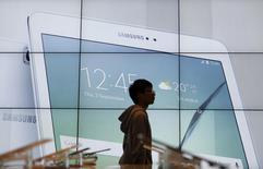 Студент проходит мимо экрана с рекламой Samsung Electronics в штаб-квартире компании в Сеуле. 27 октября 2015 года. Технологический гигант Samsung Electronics Co Ltd объявил в четверг о намерении провести обратный выкуп акций с рынка на сумму 11,3 триллиона вон ($9,9 миллиарда), сообщив ранее о росте квартальной прибыли. REUTERS/Kim Hong-Ji