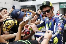Yamaha MotoGP rider Valentino Rossi of Italy signs autographs after the free practice session of the Malaysian Motorcycle Grand Prix at Sepang International Circuit near Kuala Lumpur, Malaysia, October 23, 2015. REUTERS/Olivia Harris