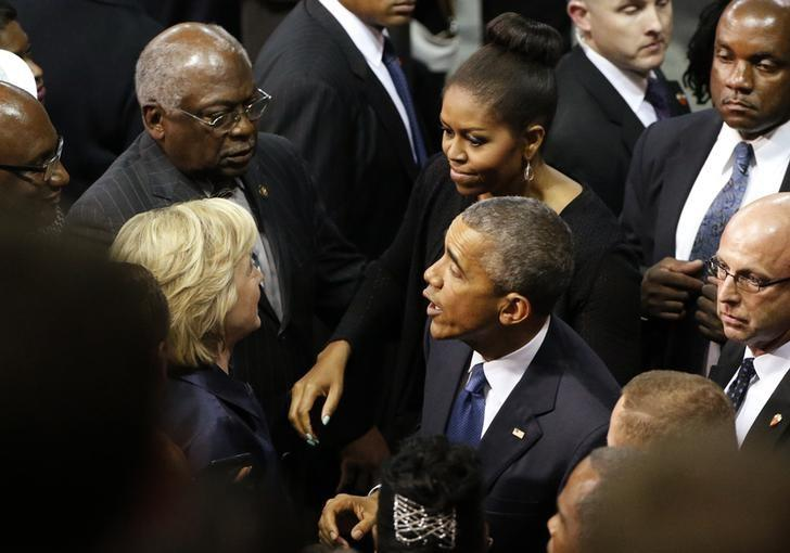 U.S. Democratic presidential candidate Hillary Clinton (L) and U.S. Rep. James Clyburn (top L) talk with first lady Michelle Obama and President Barack Obama after the conclusion of funeral services for Rev. Clementa Pinckney in Charleston, South Carolina June 26, 2015. REUTERS/Jonathan Ernst
