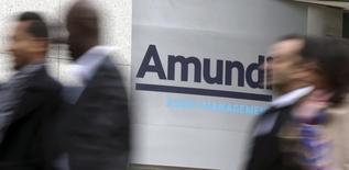 Люди проходят мимо штаб-квартиры Amundi в Париже 7 октября 2015 года. Крупнейшая в Европе управляющая компания Amundi рассчитывает привлечь порядка 2 миллиардов евро ($2,21 миллиарда) в ходе биржевого листинга, благодаря которому из капитала компании выйдет нынешний акционер - Societe Generale. REUTERS/Philippe Wojazer