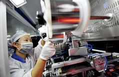 Una empleada opera maquinaria en una línea de productos de energía solar en Shangrao. 11 de octubre de 2015. La actividad de las fábricas en China disminuyó por octavo mes consecutivo en octubre, pero a una tasa menor por una recuperación de pedidos para exportación, mostró el lunes un sondeo privado, que apuntó a que la segunda economía mundial seguirá débil. REUTERS/China Daily. PARA PUBLICACIÓN FUERA DE CHINA.