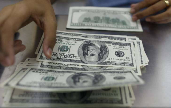 A woman counts U.S. dollars at a money changer in Yangon May 23, 2013. REUTERS/Soe Zeya Tun