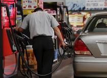 Un trabajador cargando combustible en una gasolinera en Tokio, ago 26, 2015.  Los productores de petróleo del Golfo Pérsico están aplazando parte del mantenimiento en sus campos hasta el próximo año para mantener elevada su producción y reducir costos, debido a que prevén que los precios más bajos del crudo el 2016, dijeron fuentes de la industria.  REUTERS/Toru Hanai