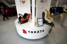 Visitors look at cars behind a logo of Takata Corp on its display at a showroom for vehicles in Tokyo, Japan, June 25, 2015. REUTERS/Yuya Shino