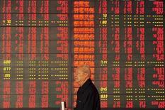 Un inversor camina delante de un tablero electrónico que muestra la información de las acciones en una correduría en Fuyang, China, 9 de octubre de 2015. Las acciones chinas registraron el miércoles su mayor ganancia diaria en siete semanas, impulsadas por las expectativas de que un vínculo comercial entre los mercados de valores de Hong Kong y Shenzhen será puesto en marcha antes de fin de año. REUTERS/China Daily