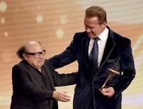 Actor Danny DeVito (L) hands over the award for life's work to Arnold Schwarzenegger at the 'Die Goldene Kamera' (Golden Camera) awards ceremony in Hamburg, February 27, 2015. REUTERS/Christian Charisius/Pool
