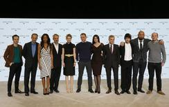 """Cast members pose on stage with director Sam Mendes during an event to mark the start of production for the new James Bond film """"Spectre"""", at Pinewood Studios in Iver Heath, southern England December 4, 2014. (L-R) Andrew Scott, Ralph Fiennes, Naomie Harris, director Sam Mendes, Lea Seydoux, Daniel Craig, Monica Bellucci, Christoph Waltz, Ben Whishaw, Dave Bautista and Rory Kinnear.  REUTERS/Stefan Wermuth"""