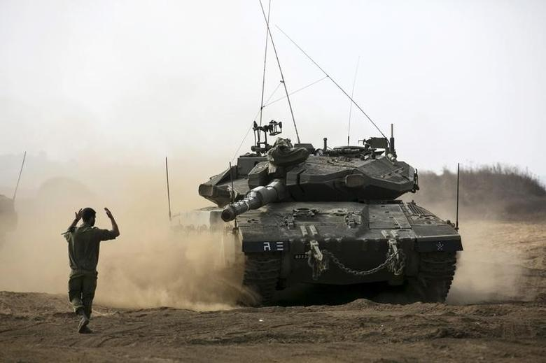 An Israeli soldier directs a tank during an exercise in the Israeli-occupied Golan Heights, near the ceasefire line between Israel and Syria, August 21, 2015. REUTERS/Baz Ratner