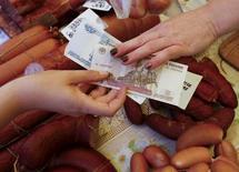Продавец на рынке в Красноярске берет деньги у покупателя. 29 июля 2015 года. Потребительские цены в России в октябре 2015 года выросли на 0,7 процента в месячном и на 15,6 процента в годовом выражении, как и ожидали опрошенные Рейтер аналитики. REUTERS/Ilya Naymushin
