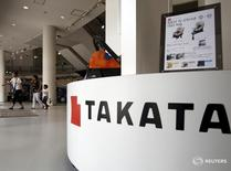 Visitors walk behind a logo of Takata Corp on its display at a showroom for vehicles in Tokyo, Japan, June 25, 2015.  REUTERS/Yuya Shino -
