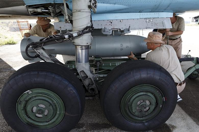 Russian ground staff members load a Sukhoi Su-34 fighter jet with weapons at the Hmeymim air base near Latakia, Syria, in this handout photograph released by Russia's Defence Ministry October 22, 2015. REUTERS/Ministry of Defence of the Russian Federation/Handout via Reuters