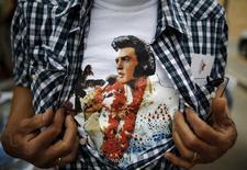 """Un fan de Elvis Presley muestra su camiseta con una imagen del cantante, en un festival musical de Collingwood, Ontario, el 25 de julio de 2015. Casi 40 años después de su muerte, Elvis Presley ha vuelto a la cima de las listas de álbumes más vendidos en Reino Unido con su décimosegundo número 1 británico """"If I Can Dream"""", una colección de clásicos que presenta nuevos arreglos de la Royal Philharmonic Orchestra. REUTERS/Chris Helgren"""
