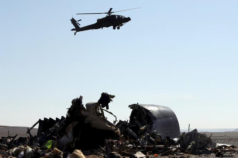 An Egyptian military helicopter flies over debris from a Russian airliner which crashed at the Hassana area in Arish city, north Egypt, November 1, 2015.  REUTERS/Mohamed Abd El Ghany