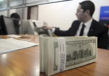 Un empleado de una casa cambiaria cuenta dólares estadounidenses en un banco en El Cairo, 31 de diciembre de 2013. El dólar tocó el martes nuevos máximos de siete meses, impulsado por la ampliación en los diferenciales de las tasas de los bonos del Tesoro estadounidense por expectativas de que la Reserva Federal suba las tasas de interés el mes próximo. REUTERS/Stringer