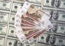 Рублевые и долларовые купюры в Сараево 9 марта 2015 года. Рубль начал торги среды ослаблением к евро, отыгрывая укрепление единой валюты на форексе и снижение цены нефти, при этом изменения против доллара минимальные, что участники рынка связывают с продажами экспортной выручки на фоне низкой спекулятивной активности из-за выходного дня в США. REUTERS/Dado Ruvic