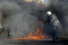 Греческий полицейский в Афинах. 12 ноября 2015 года. Жители Греции вышли на забастовку в четверг в знак протеста против мер жесткой экономии, бросая правительству Алексиса Ципраса крупнейший внутренний вызов со времени его переизбрания в сентябре благодаря обещанию смягчить воздействие экономических трудностей. REUTERS/Michalis Karagiannis