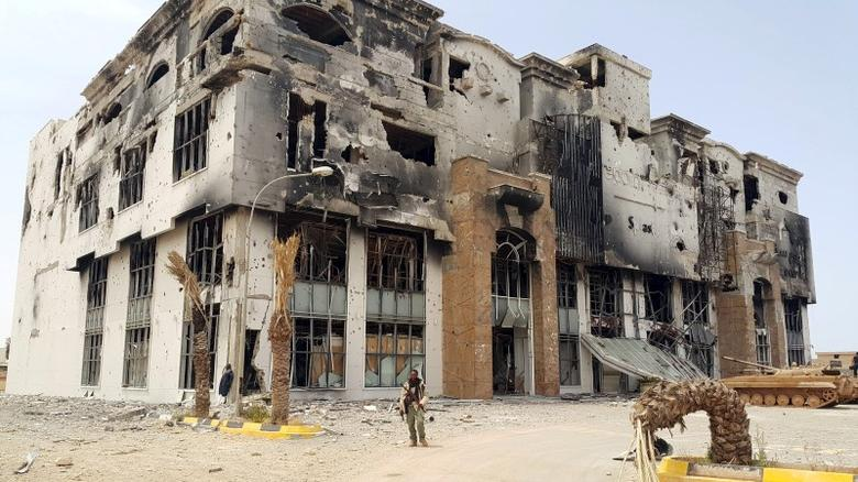 A member of the Libyan pro-government forces stands in front of the ruins of a shopping mall in Benghazi, Libya, May 21, 2015.  REUTERS/Stringer