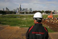 A Japan Sport Council official overlooks the empty site of the planned national stadium, the centrepiece of the Tokyo 2020 Olympics, in Tokyo, November 16, 2015. REUTERS/Thomas Peter