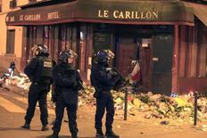"""Полицейские у ресторана Le Carillon в Париже. 15 ноября 2015 года. Французские военные самолеты нанесли удары по позициям """"Исламского государства"""" в Сирии в воскресенье, в то время как полиция в Европе расширила расследование скоординированных атак в Париже, в результате которых погибли более 130 человек. REUTERS/Pascal Rossignol"""