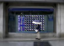 Una mujer mira un tablero que muestra información bursátil, afuera de una correduría en Tokio, 8 de septiembre de 2015. Las bolsas de Asia caían el lunes a mínimos en seis semanas y las monedas de mercados emergentes se debilitaban en momentos en que los inversores buscaban la seguridad de la divisa estadounidense luego de los ataques del viernes en París y tras unos datos económicos pesimistas. REUTERS/Issei Kato