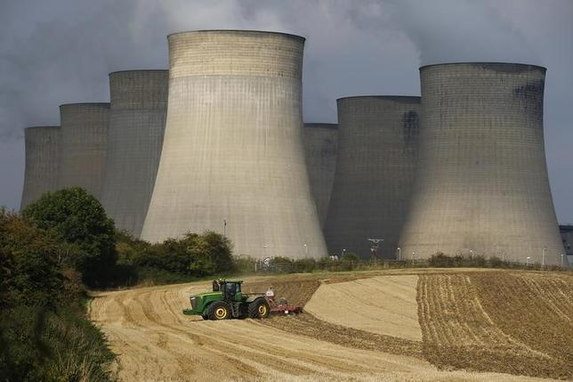 A farmer works a field in the shadows of Ratcliffe-on-Soar Power Station in central England, in this September 10, 2014 file photo. REUTERS/Darren Staples