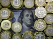 Монеты номиналом 100 тенге и купюра в 100 долларов США в Алма-Ате 6 ноября 2015 года. Национальный банк Казахстана, новому главе которого поручено вернуть доверие национальной валюте, заявил в среду, что не допустит резких и дестабилизационных изменений обменного курса тенге. REUTERS/Shamil Zhumatov